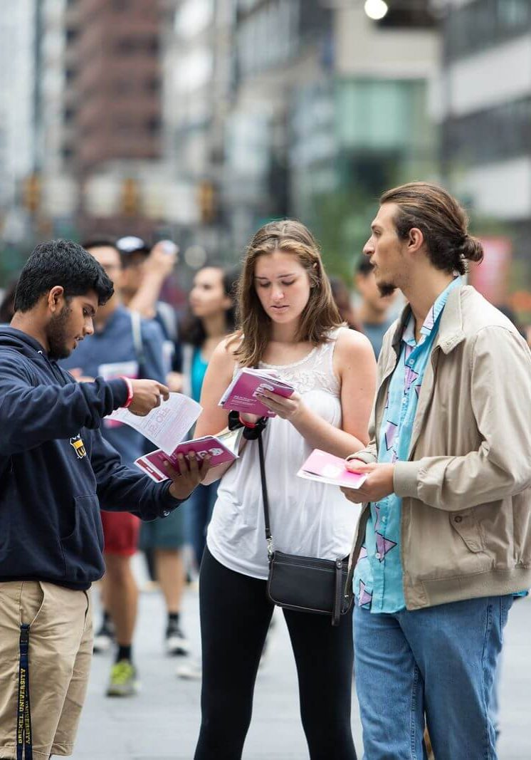 Campus Philly students holding brochure on an event